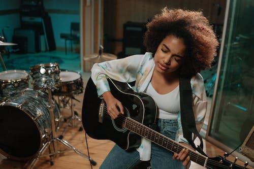 Woman in White Blazer Playing Guitar