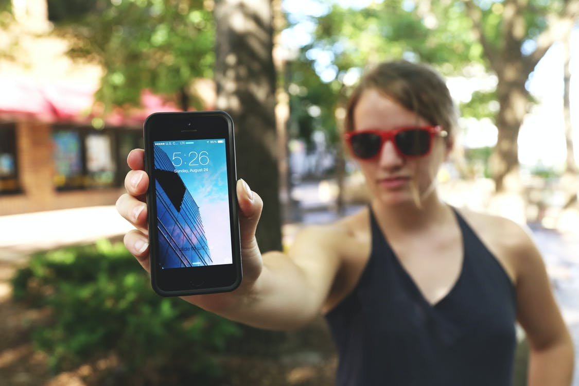 Woman Wearing Black Spaghetti Strap Top and Sunglasses Standing While Holding Space Gray Iphone 5s