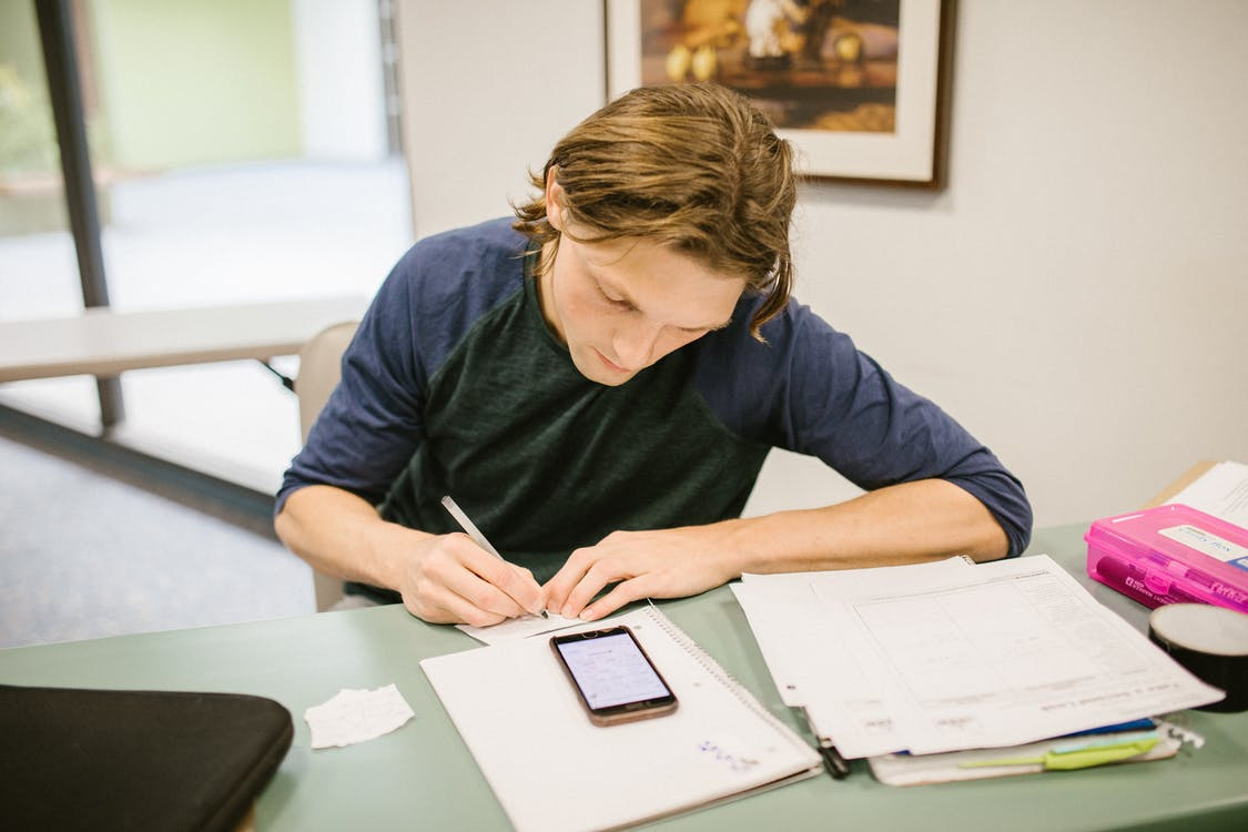 Man in Blue Long Sleeve Shirt Writing on White Paper