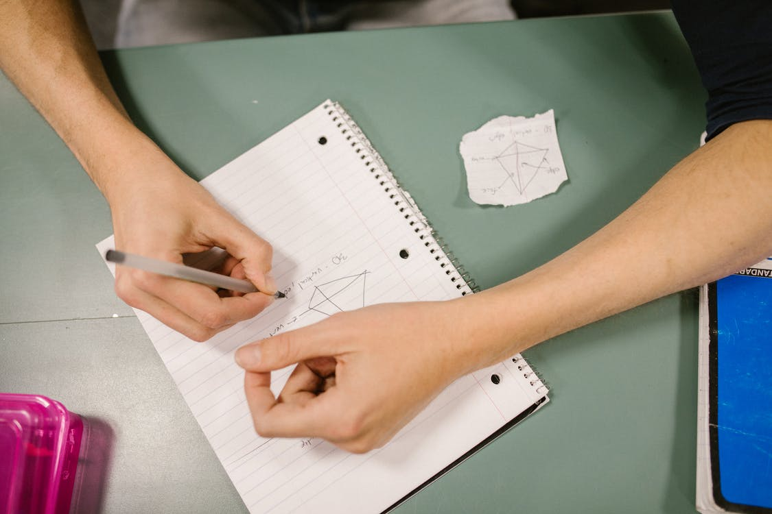Student Making a Cheat Sheet on a Piece of Paper