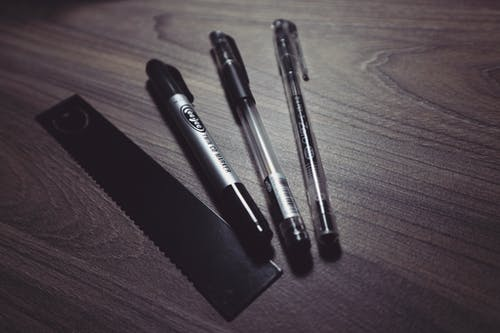 Three Ballpoint Pens and Black Ruler on Beige Wooden Surface