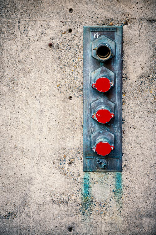 Shabby metal components of city fire suppression system on aged concrete wall in daytime