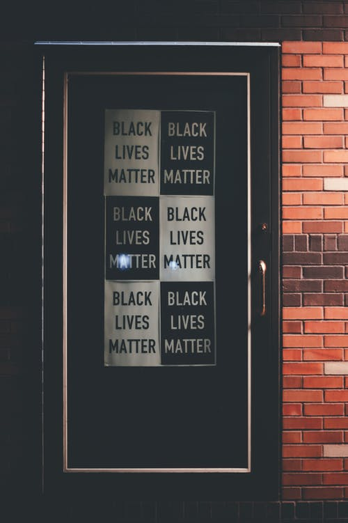 Exterior fragment of brick building with printed Black Lives Matter signboards on door