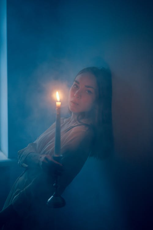 Young woman with candle in dark room