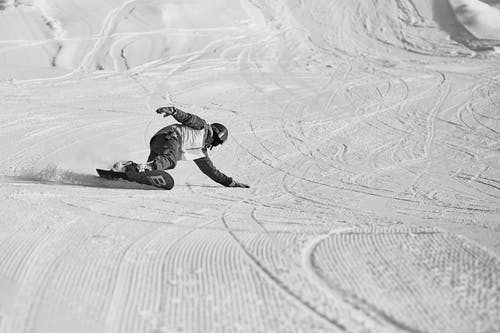 From above of anonymous snowboarder in helmet and protective equipment sliding down on snowy slope