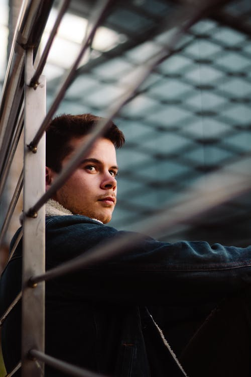 Low angle of young pensive male in denim jacket looking away while sitting near metal fence under glass roof in daylight