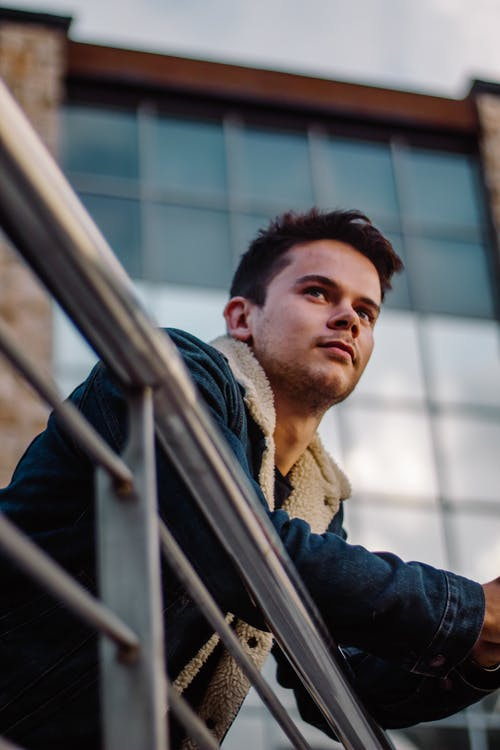 Low angle of focused young male in trendy denim jacket leaning on handrail with arms and thoughtfully looking away