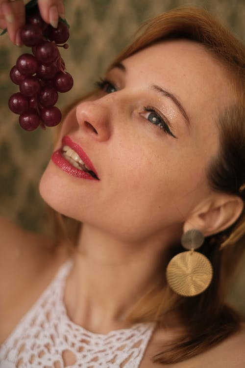 Crop female with eyeliner and lipstick on face eating fresh purple grapes on blurred background