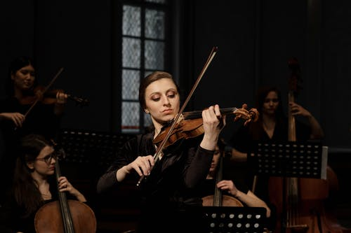Woman Playing Violin in Front of People