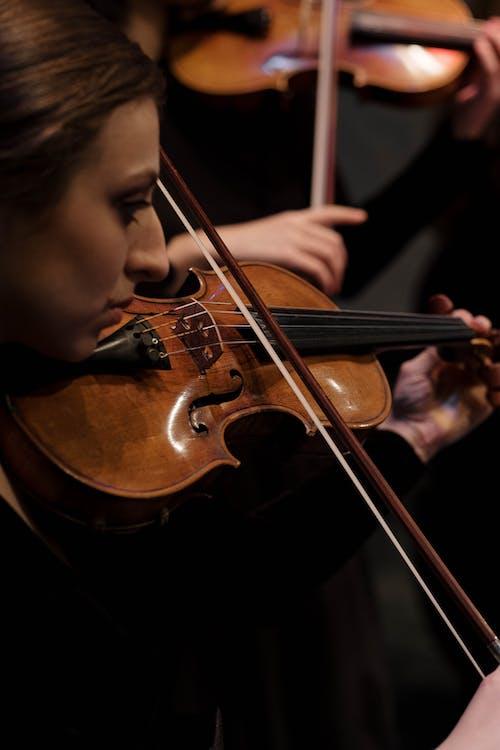 Boy Playing Violin in Black Room