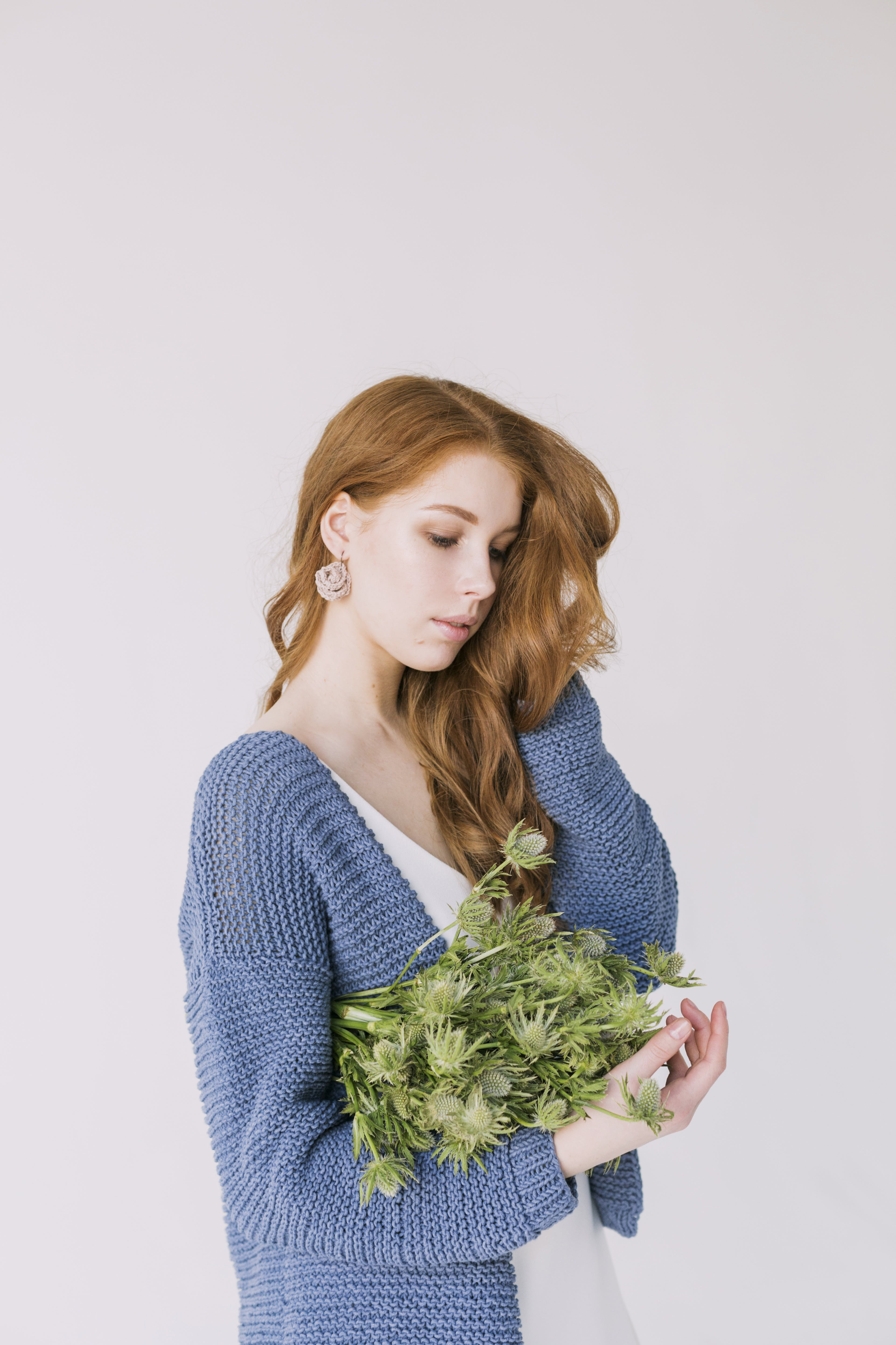 Woman in Blue Cardigan Holding Green Flowers