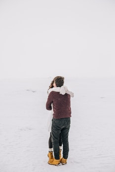 Man and Woman Kissing on Snow Field