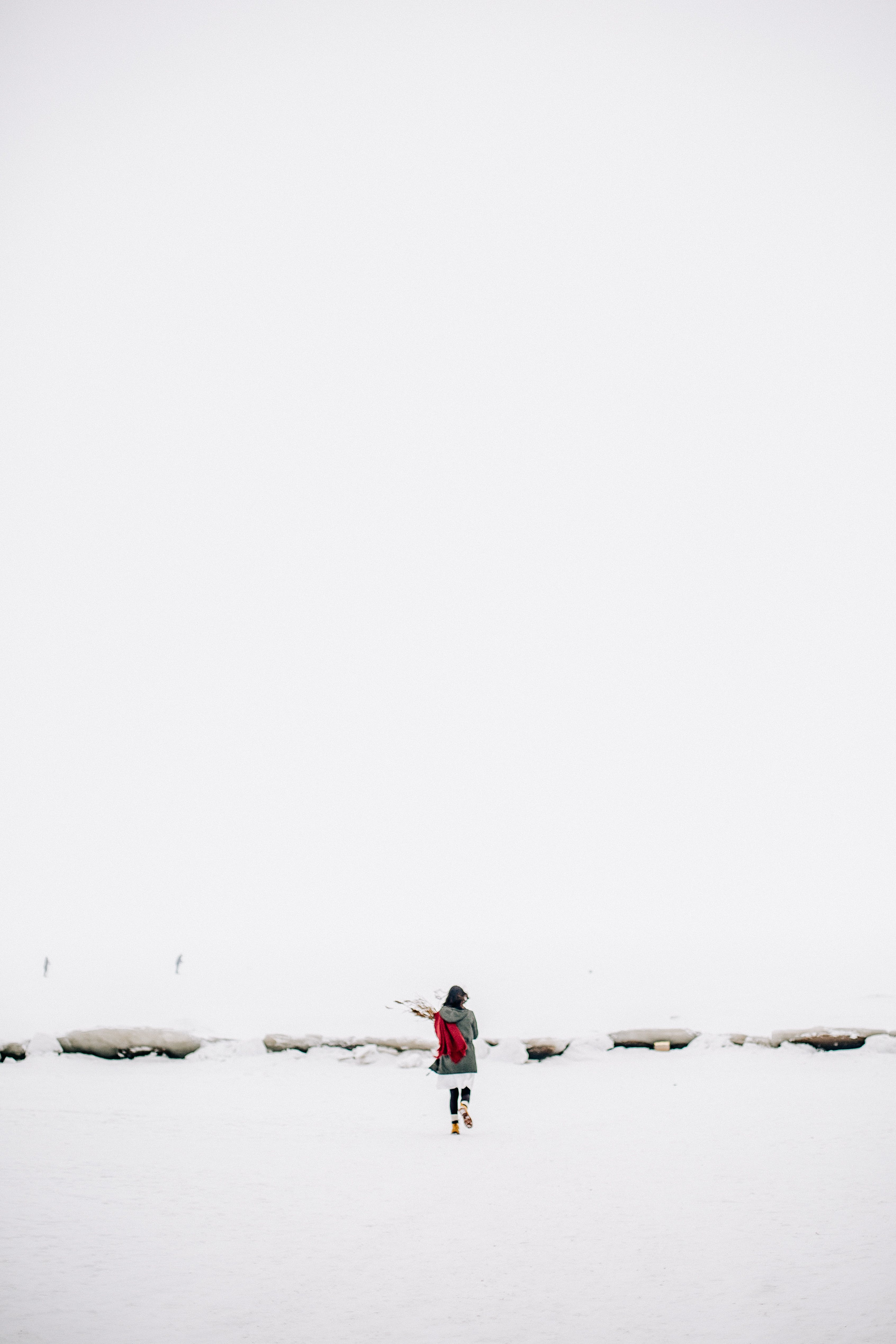 Woman Walking on Snow-covered Field