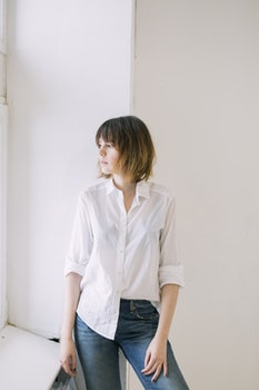 Woman in White Dress Shirt and Blue Jeans