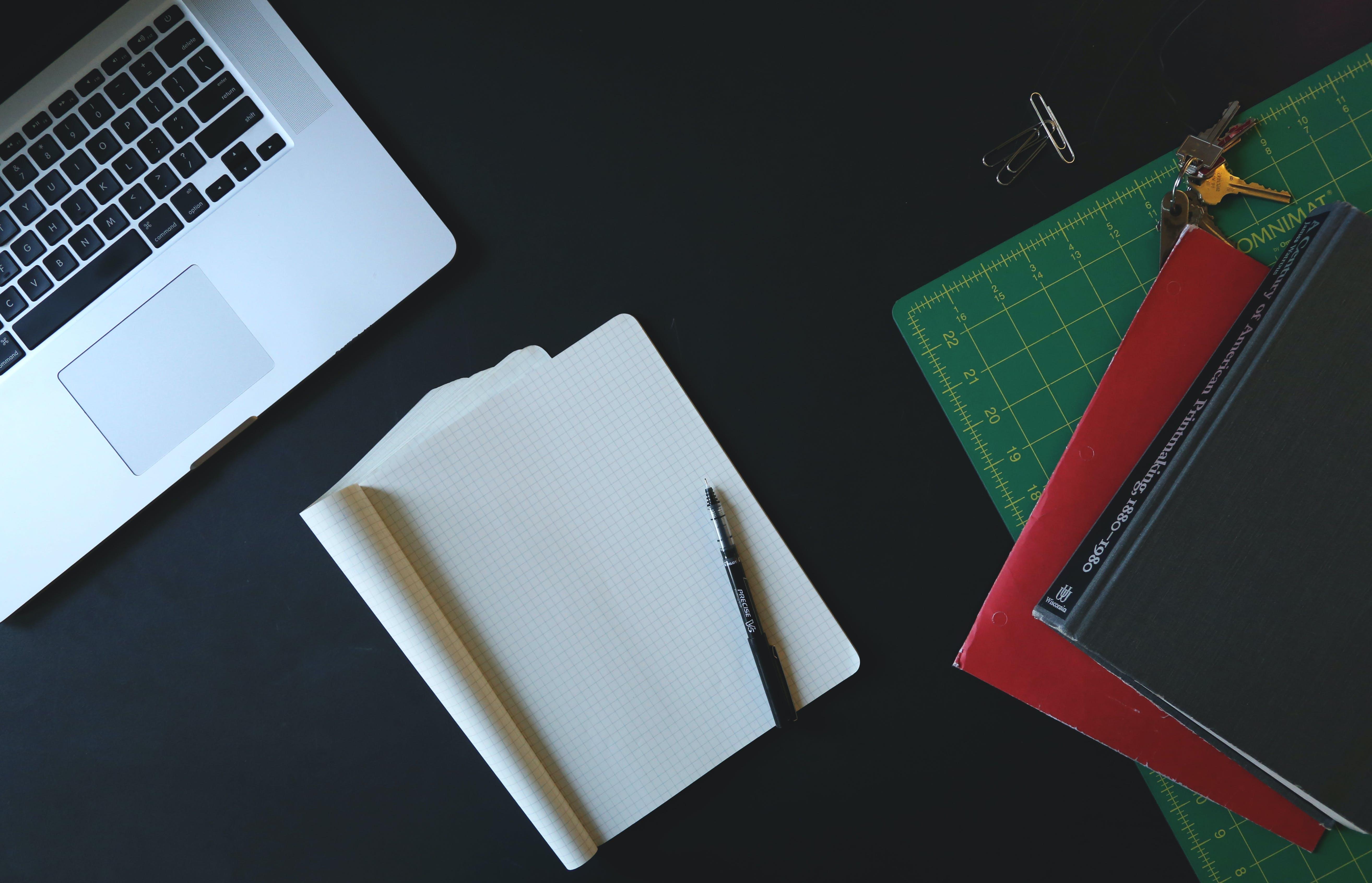 White Printer Paper Beside Macbook Pro on Black Surface