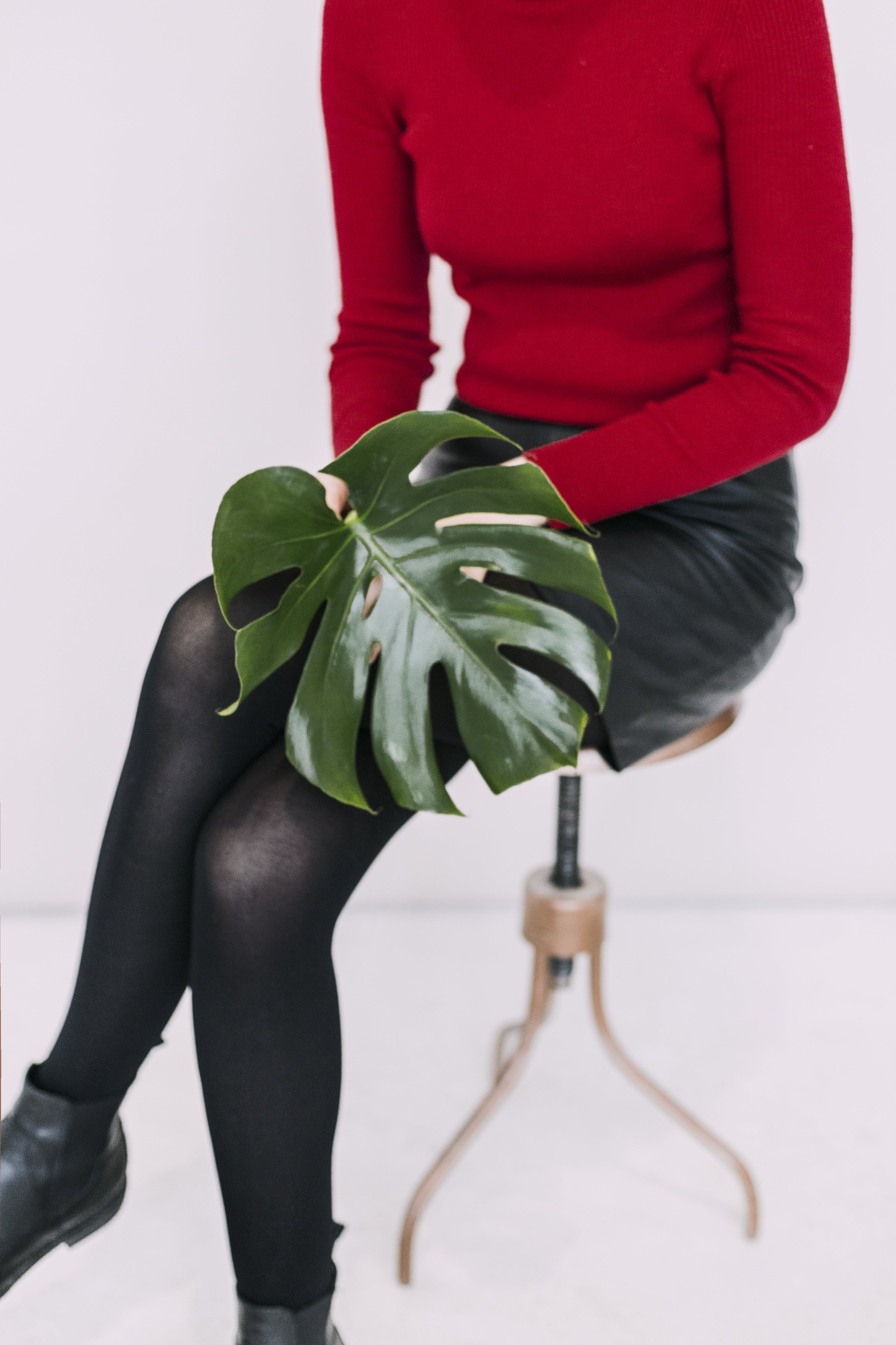Woman in Red Sweater and Black Pants Holding Green Leaf
