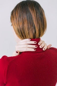 Woman in Red Turtle-neck Shirt Touching Her Neck