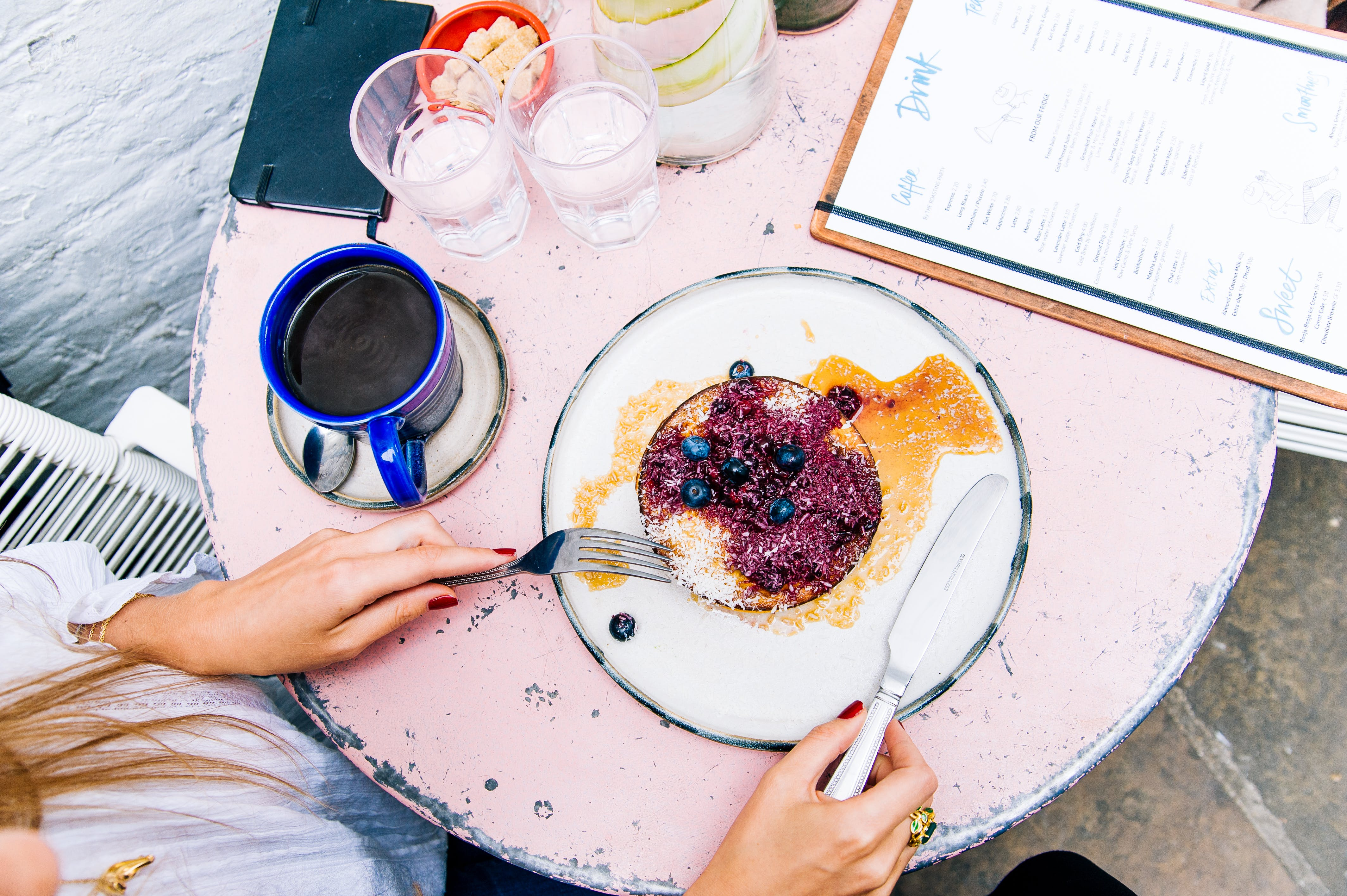 Woman Holding Spoon and Fork With Blackberries on Plate Beside Blue Ceramic Mug on White Wooden Table