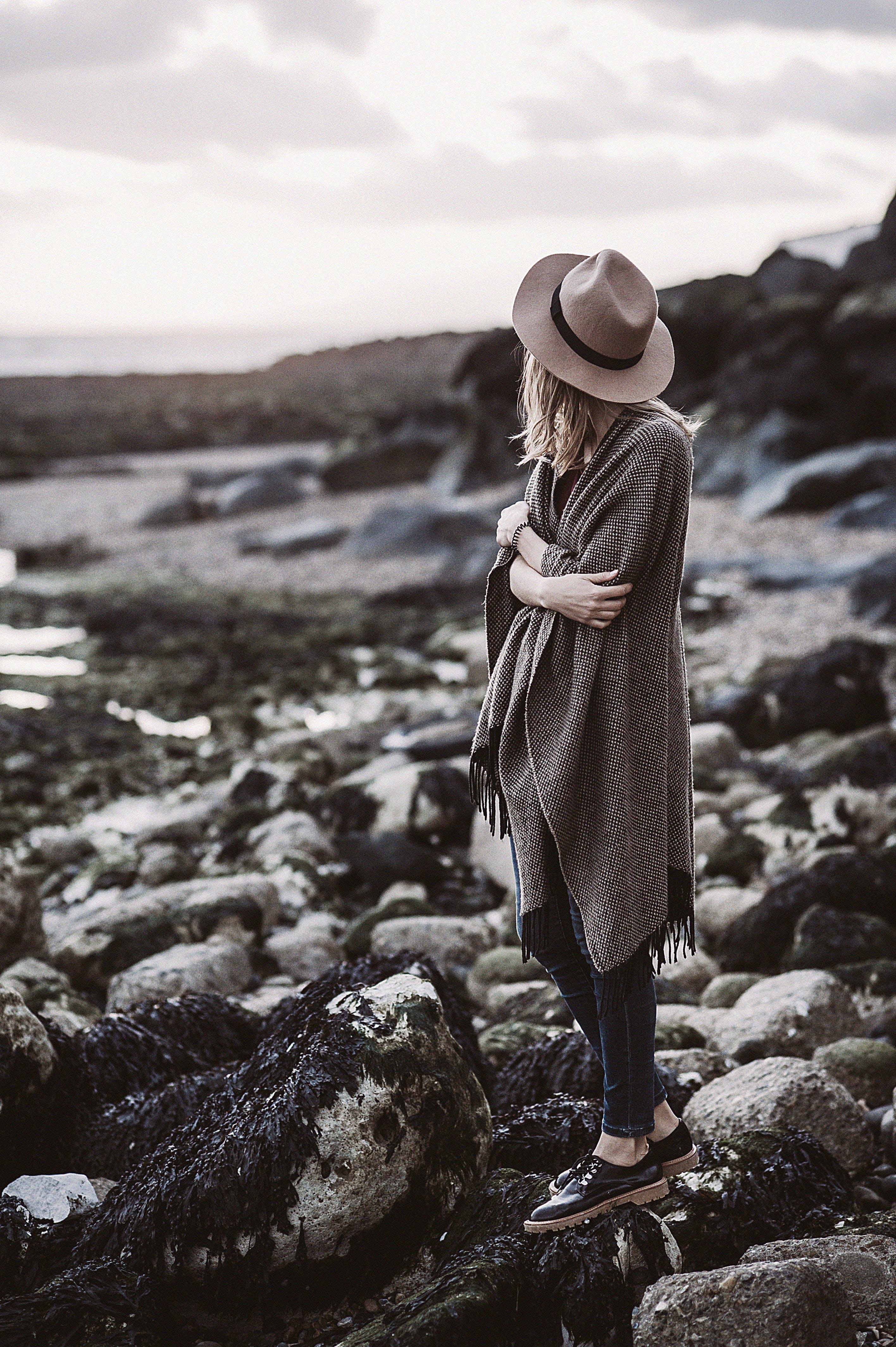 Woman Wearing Draped Coat Standing on Rock Facing Mountain