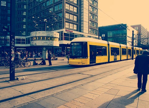 Selective Color Photography of Yellow Train Near Concrete Buildings