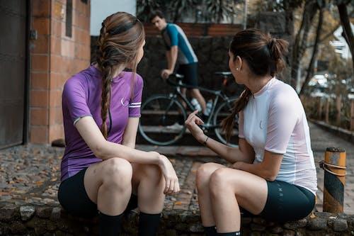 Anonymous female friends in sportswear sitting on step near walkway in town street near cyclist with bike in daytime