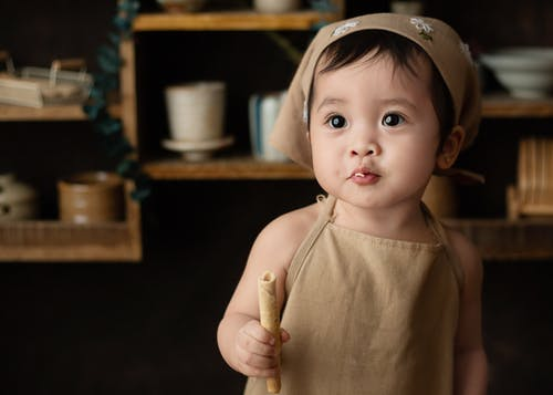 Adorable Asian toddler in apron eating tasty sweet wafer roll in kitchen and looking away