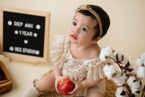 From above of sweet Asian toddler in dress and with apple sitting in studio and looking up