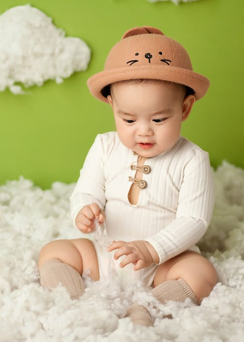 Adorable Asian baby sitting in soft fluffy clouds in studio on green background