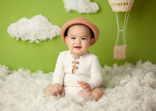Cheerful ethnic baby sitting in clouds in studio