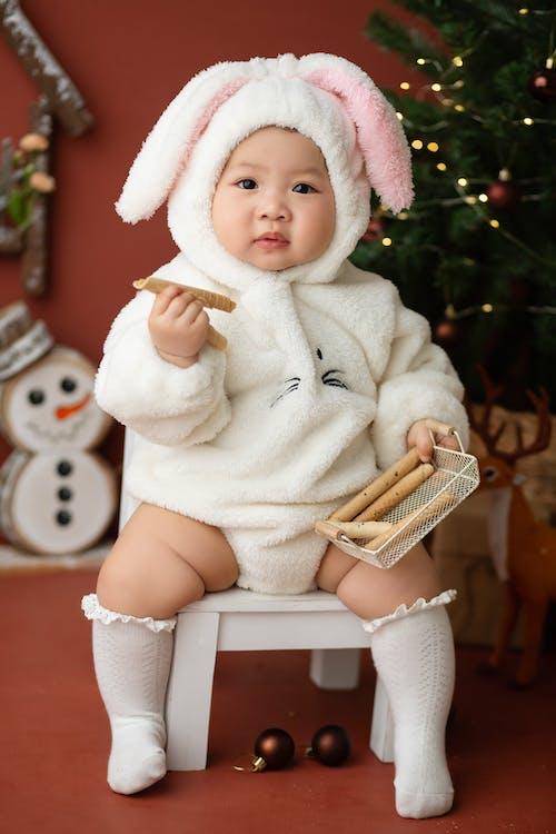 Cute ethnic toddler in bunny costume in studio
