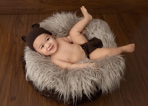 From above of Asian little child lying in soft nest in studio and looking away
