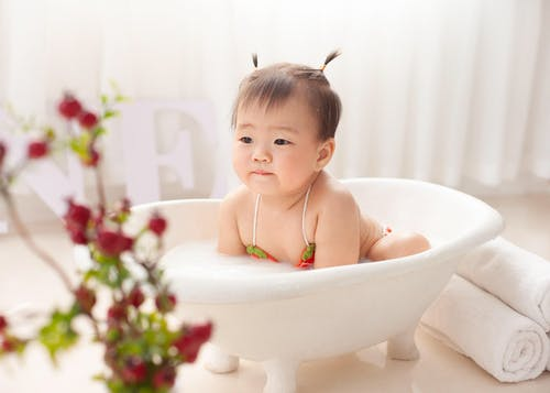 Sweet Asian little girl in swimwear sitting in small bathtub and bathing at home