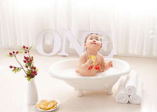 Adorable ethnic little girl in bathtub