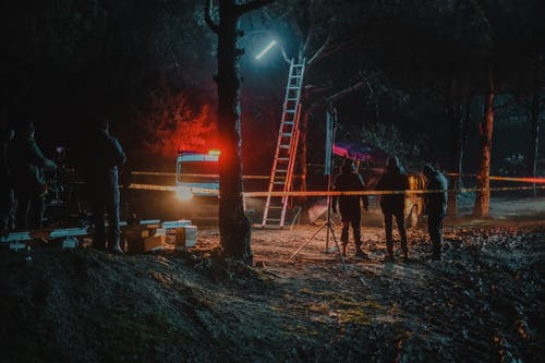 Group of colleagues investigating crime scene fenced with tape among trees at dark night