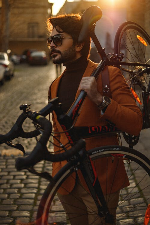 Side view of serious bearded male in elegant clothes standing on paved sidewalk while carrying bicycle on shoulder in evening city