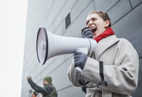 Man in Gray Coat Holding White and Gray Speaker