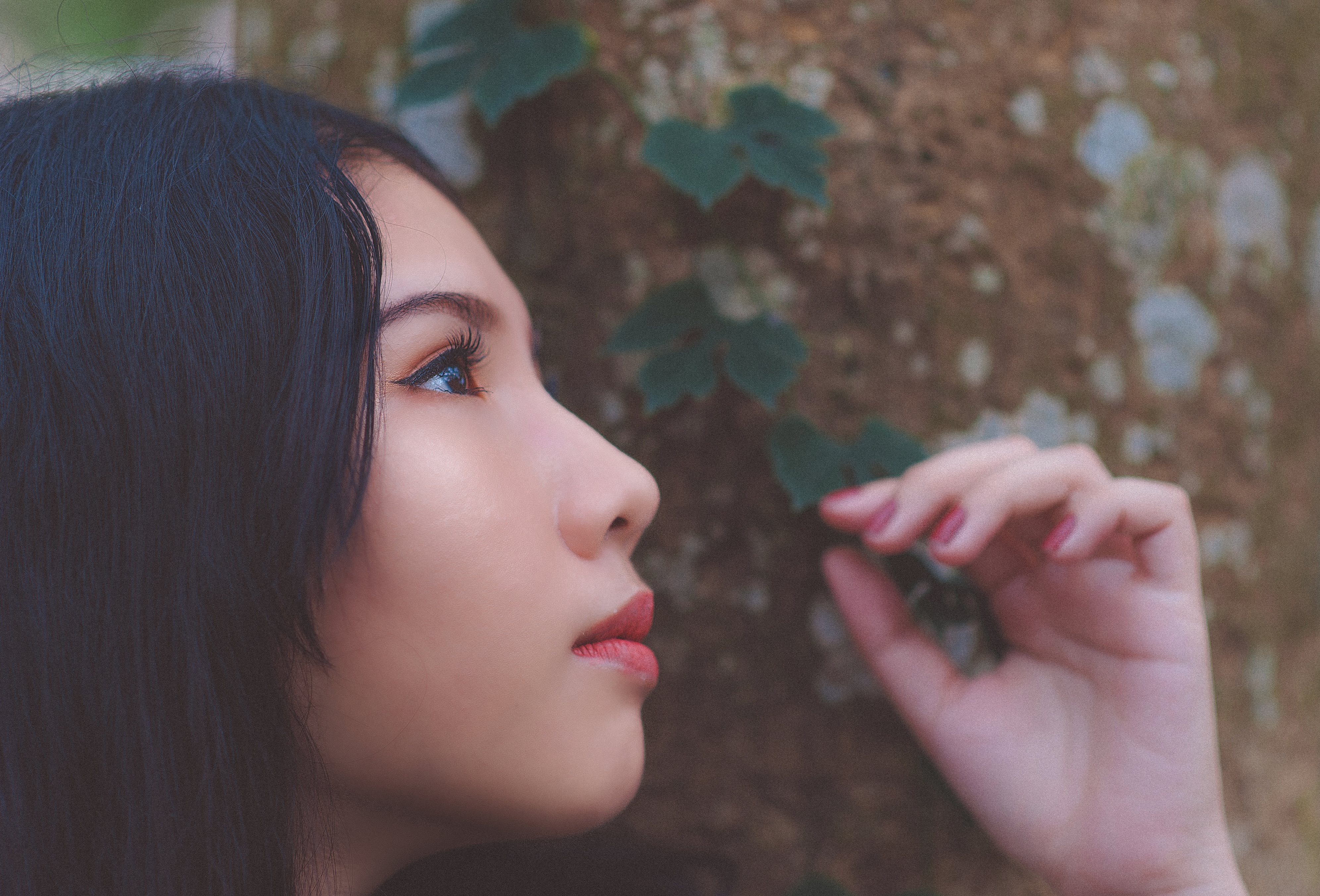 Close Up Photo of Woman Looking Up Near Tree Trunk
