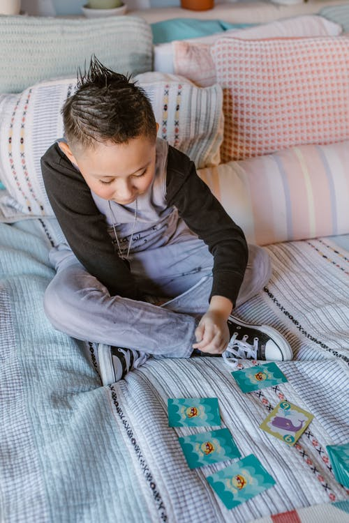 Attentive boy sitting on bed and playing card game at home