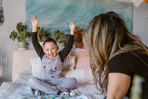 Happy boy raising arms after winning card game sitting on bed with unrecognizable mother