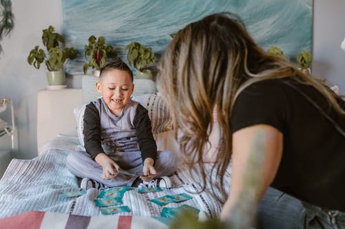 Cheerful kid playing cards game with unrecognizable mom on bed