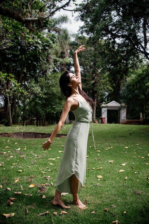 Woman in White Spaghetti Strap Dress Standing on Green Grass Field