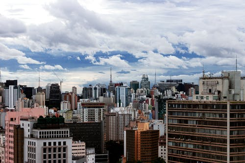 City Buildings Under White Clouds and Blue Sky