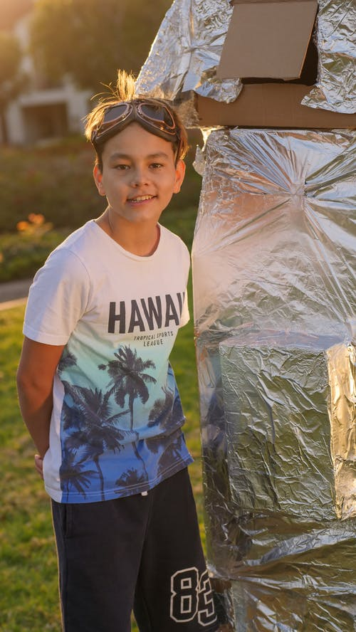 Boy in White and Blue Crew Neck T-shirt Standing Beside Gray Plastic Bag