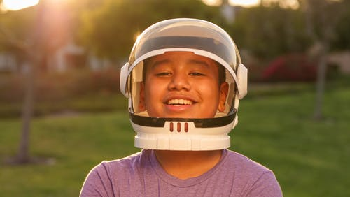 Smiling Girl in Purple Shirt Wearing White Helmet
