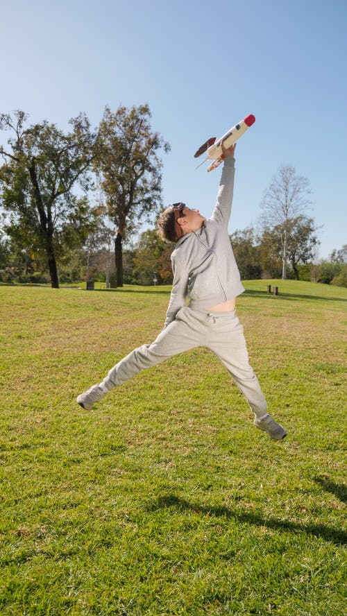 Man in White Long Sleeve Shirt and White Pants Jumping on Green Grass Field