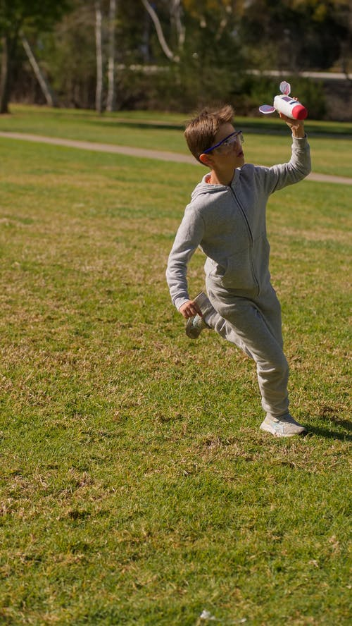 Boy in White Long Sleeve Shirt and White Pants Walking on Green Grass Field