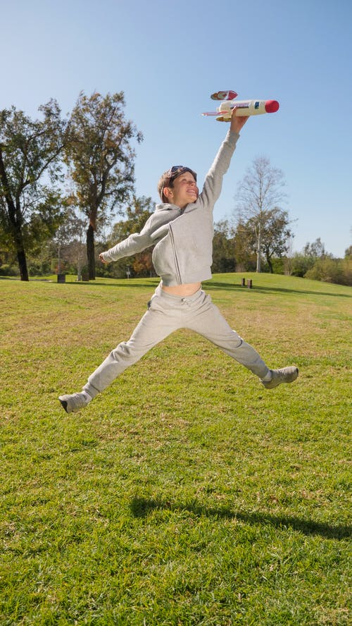 Woman in White Long Sleeve Shirt and White Pants Jumping on Green Grass Field