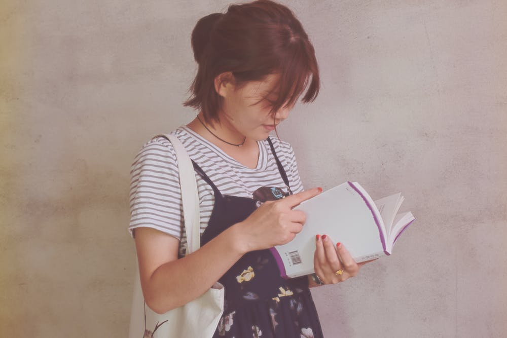 Girl holding a white book. | Photo: Pexels
