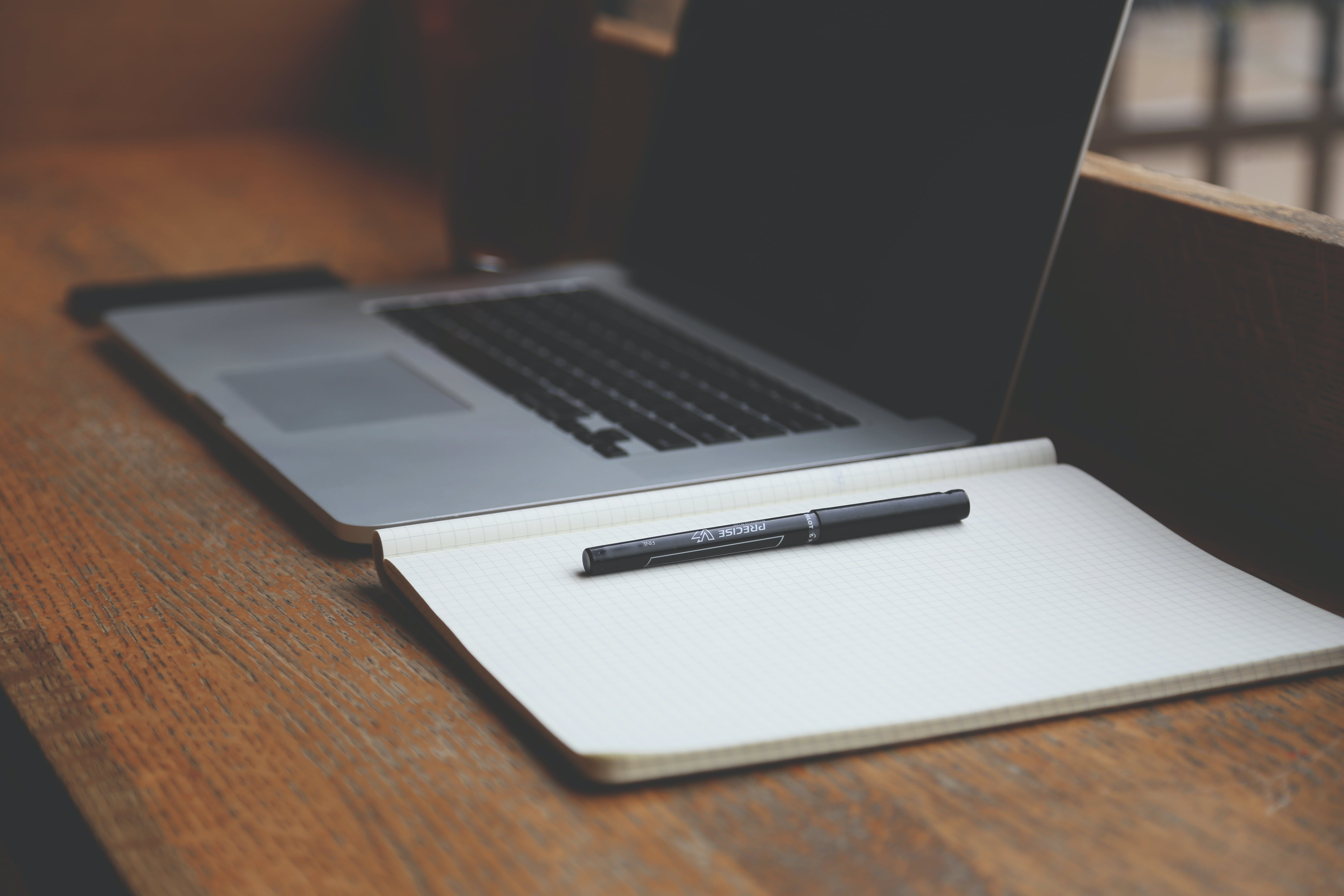 Macbook Pro Beside Book and Pen