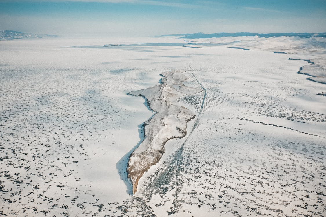 Drone view of rocky formation on icy ocean with snow under cloudy sky in wintertime